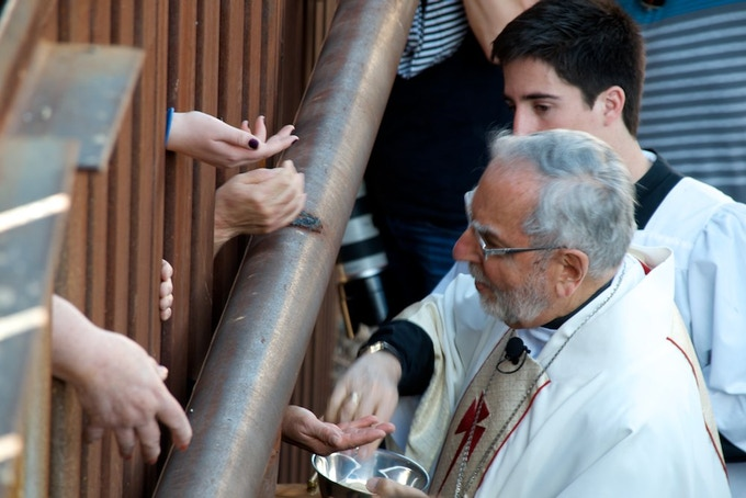 Cardinal Sean O'Malley hands out communion wafers through the fence that cuts Ambos Nogales in two. The communion was part of a mass, held in the city during a border tour by seven Catholic bishops. Photo by Paul Ingram/TucsonSentinel.com