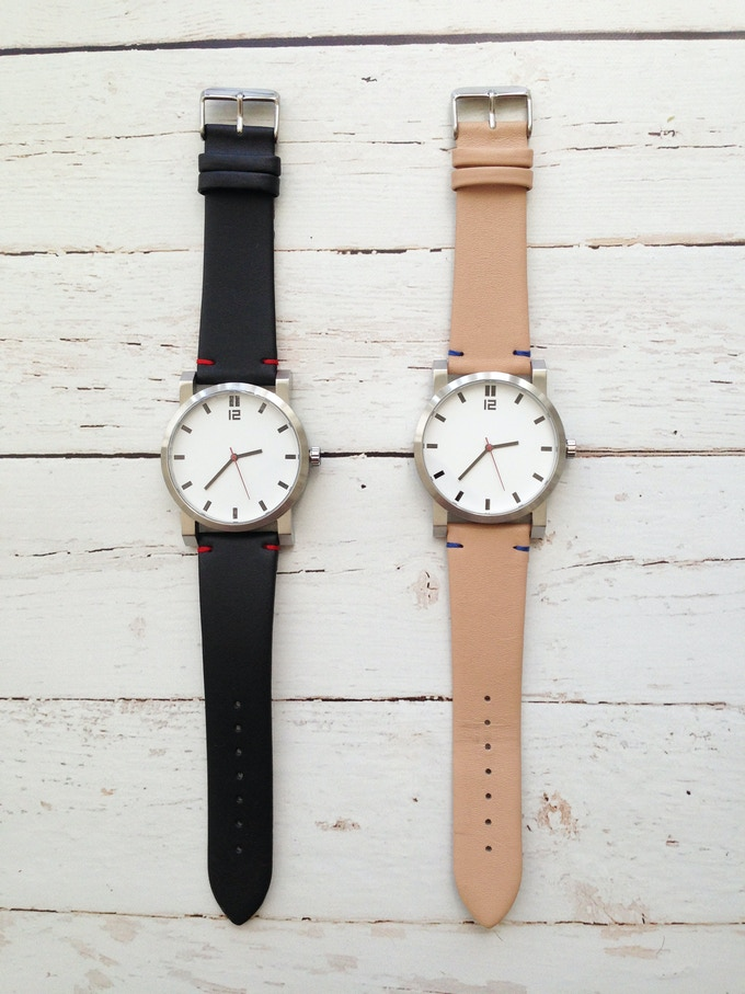 White dial with black hour markers on either a black leather watch strap or a natural leather watch strap.