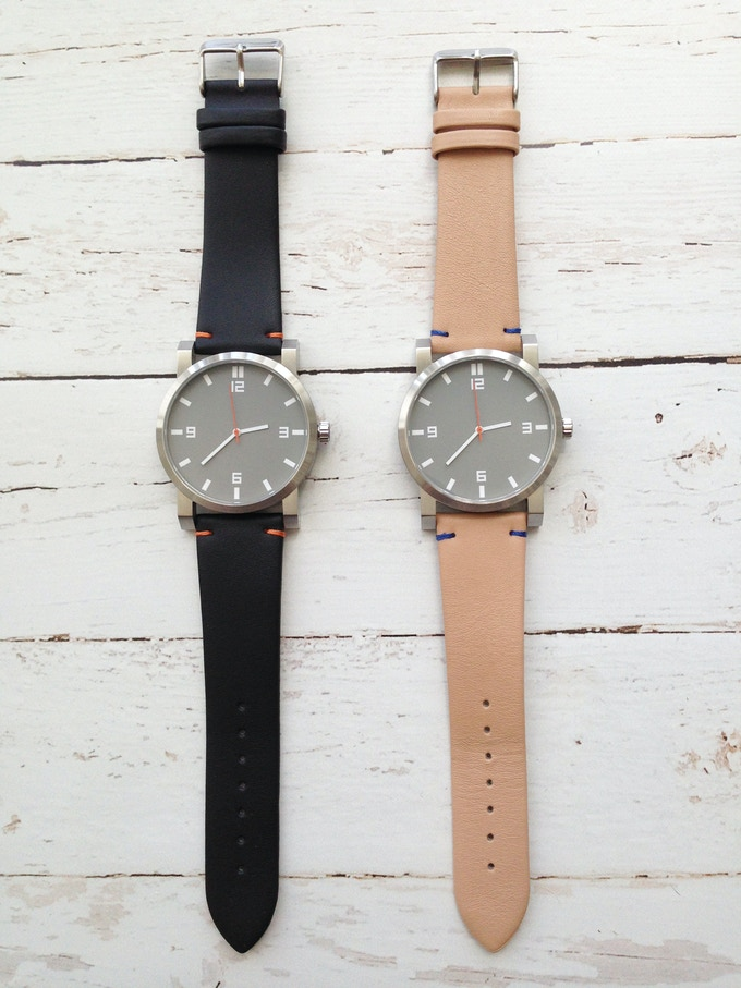 Grey dial with white Arabic hour makers on either a black leather watch strap or natural leather watch strap.