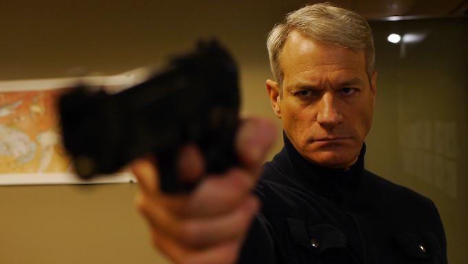 Frank Taylor (Steve Mattsson) aims a gun in the Clone Assassin episode