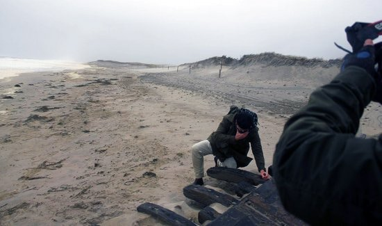 Actor Chris Kolb, portraying Henry Beston, comes upon the remains of the wreck of the Montclair during a nor'easter on Nauset Beach in Orleans.