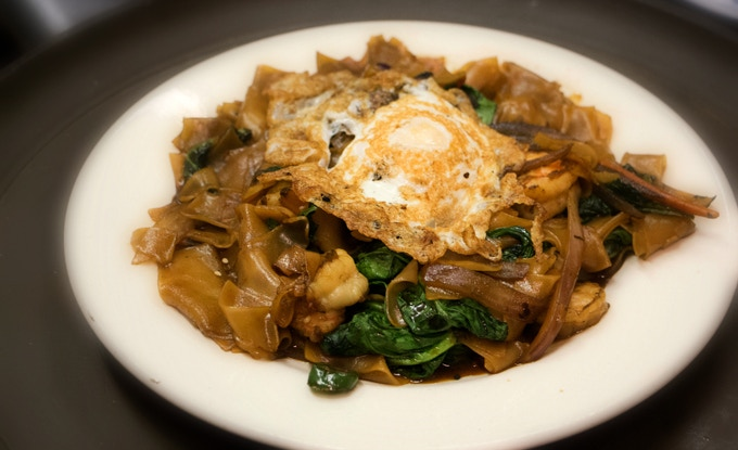Pad See Ew  - wide rice noodles stir fried in brown sauce with baby spinach, carrots, and a fried egg