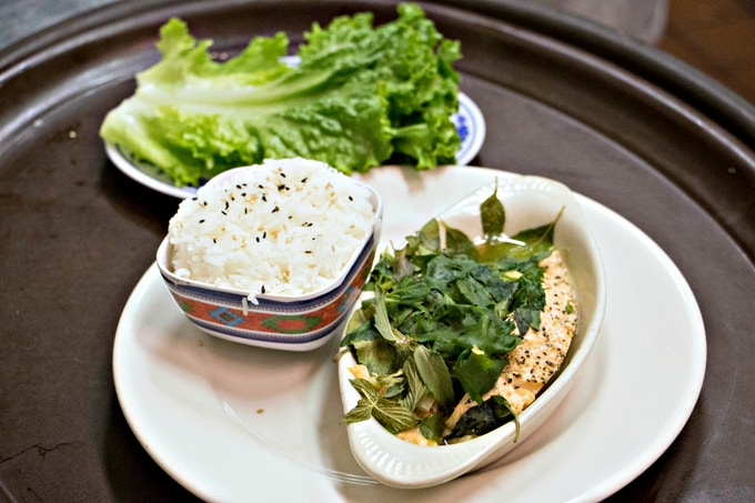 Vietnamese Steamed Salmon - a filet braised in a special brown sauce then steamed with ginger, scallions and fresh herbs and served with lettuce leaves and sliced chilies, and a side of Jasmine rice