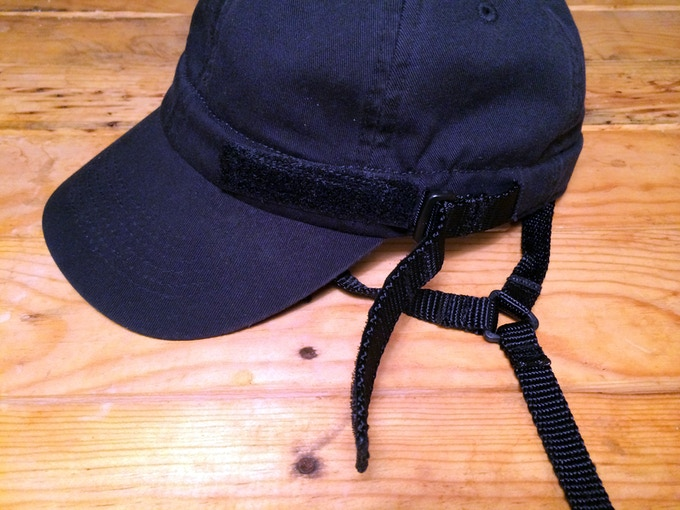 "The 3/4"" nylon head strap exits the hat, loops through a plastic square loop, and attaches with velcro to adjust tightness"