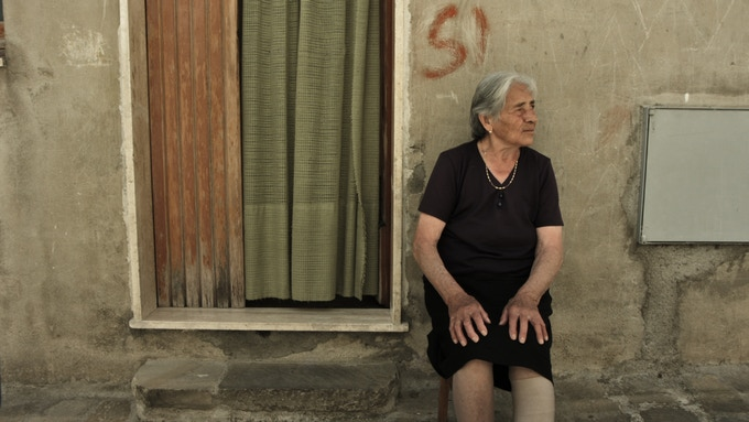Lady in mourning, sitting in the street, Vaglio (Basilicata)