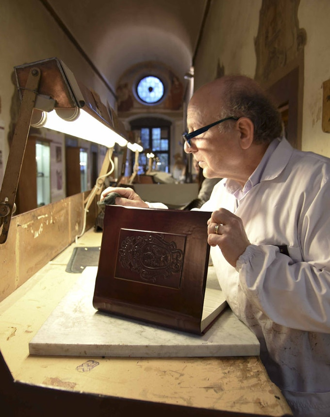 An experienced artisan creating a leather book of the type that will be used for our archival thank-you