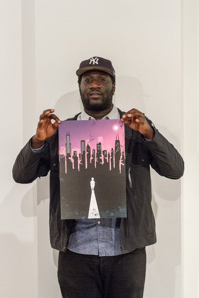 Designer Ishmael Adams stands with his poster design.