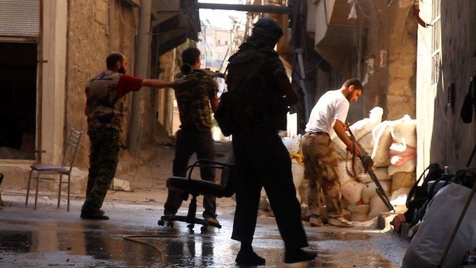 From left to right: Issa Aiash, 30, father of three, his young brother Ahmed, 17, and Sheihk Mamoud, 42, father of a newborn son. They laugh and joke as they clean their post on a backstreet of Aleppo, Syria. (Tracey Shelton - GlobalPost)