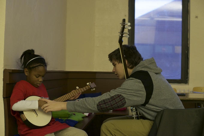 A student learning the banjo in the Cass Corridor neighborhood