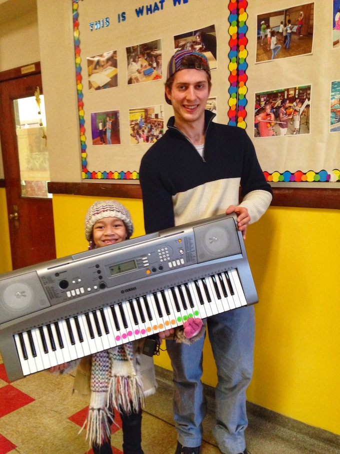 A student earning her own keyboard to take home in the Woodbridge neighborhood (with our project director Sam Saunders)