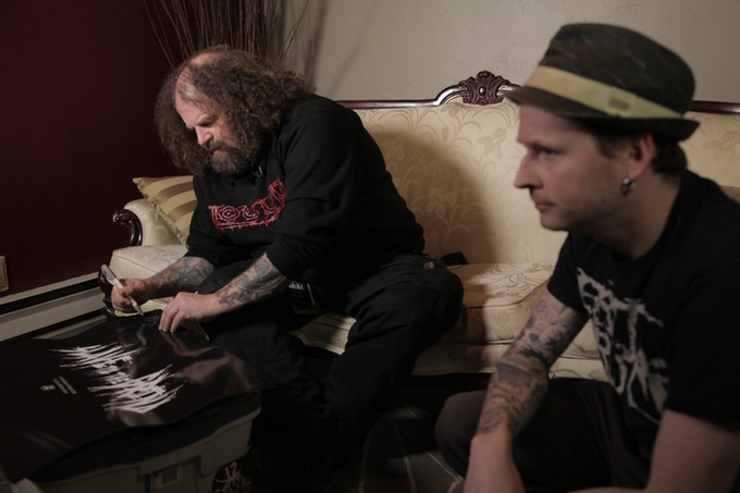 Shane Embury of Napalm Death signs the 'Grind Your Fucking Head In' poster