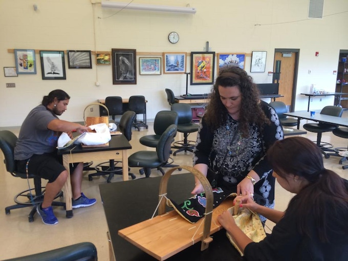 Rachel Limon working with students finishing up their cradle bags and attaching them to the cradleboard.