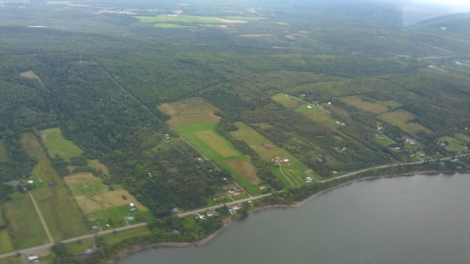 Aerial view of Point La Nim.  Maccurdy Farm is in the middle, and the woodlot stretches beyond the long road that runs back beyond the fields.