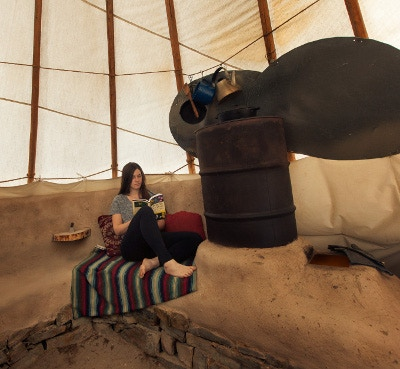 the completed cob style rocket mass heater in the tipi