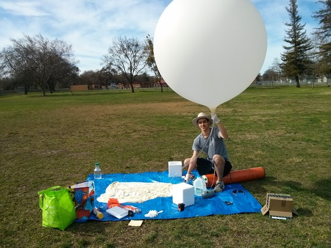 An engineer filling up a space balloon that can carry a potato payload.