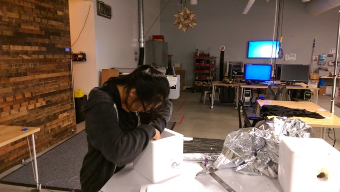 Engineer in the lab seemingly focused on assembling a balloon payload, but actually thinking about potatoes.