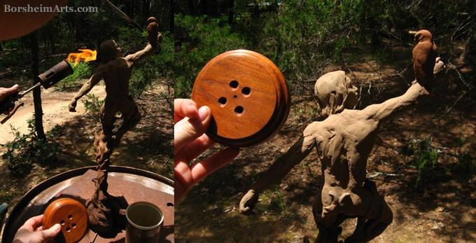 """A torch is used to create a patina on the bronze sculpture """"Warrior Spirit,"""" matching the wooden base for the artwork."""