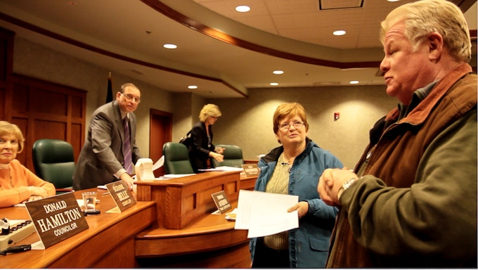 Screenshot from the film. Terry and Emma at the Town Board meeting where the moratorium was extended.