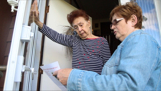 Screenshot from the film. Emma talking to one of the neighbors explaining what they plan to do with the farm and barn and asking for support before the Town Board of Appeals meeting.