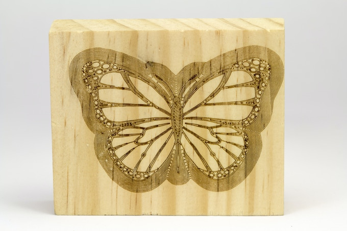 A laser etched butterfly on Pine wood with BoXZY