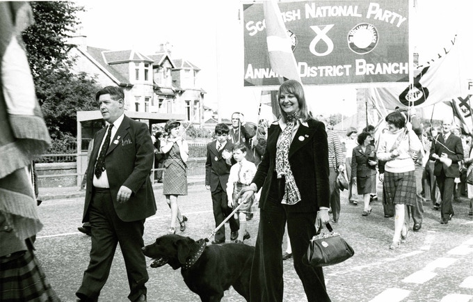 Willie McRae, Margaret Bain (later Margaret Ewing, MP and MSP) and canis lupus familiaris/pooch (name unknown) marching Bannockburn Rally through Stirling. Copyright: Scottish Political Archive.