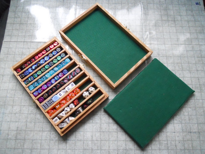 This is what you get when you pledge for a box: The bottom section with dividers, the top section with felt, and the thick felt insert to keep your dice in place.