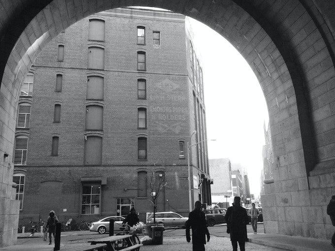 The NYC site at DUMBO, beside the gargantuan arches of the Manhattan Bridge, a vibrant digital and physical node of New York.