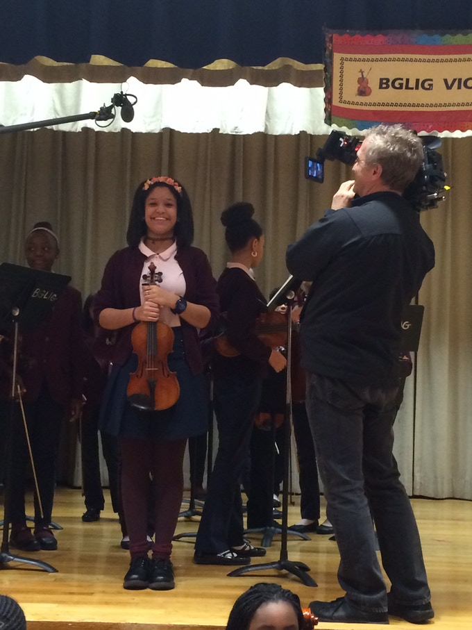 Bob films Brianna receiving the violin at BGLIG