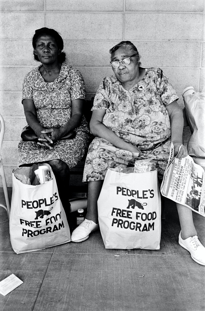 Two older women with bags from People's Free Food Program.  Photo courtesy of Stephen Shames.