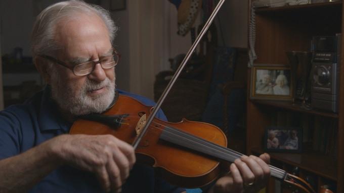 Joe at home, playing his violin.