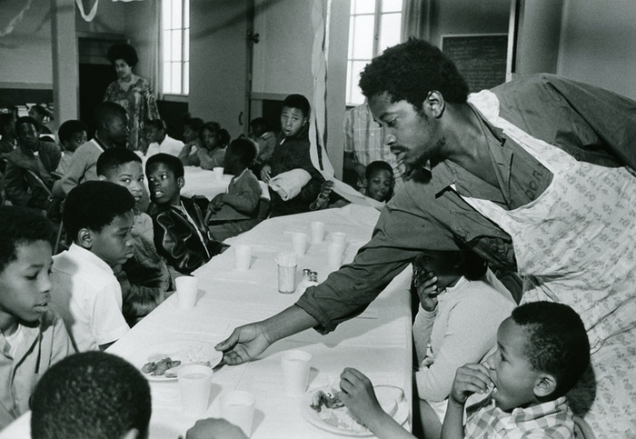 Charles Bursey hands plate of food to a child seated at Free Breakfast Program.  Photo courtesy of Pirkle Jones and Ruth-Marion Baruch.