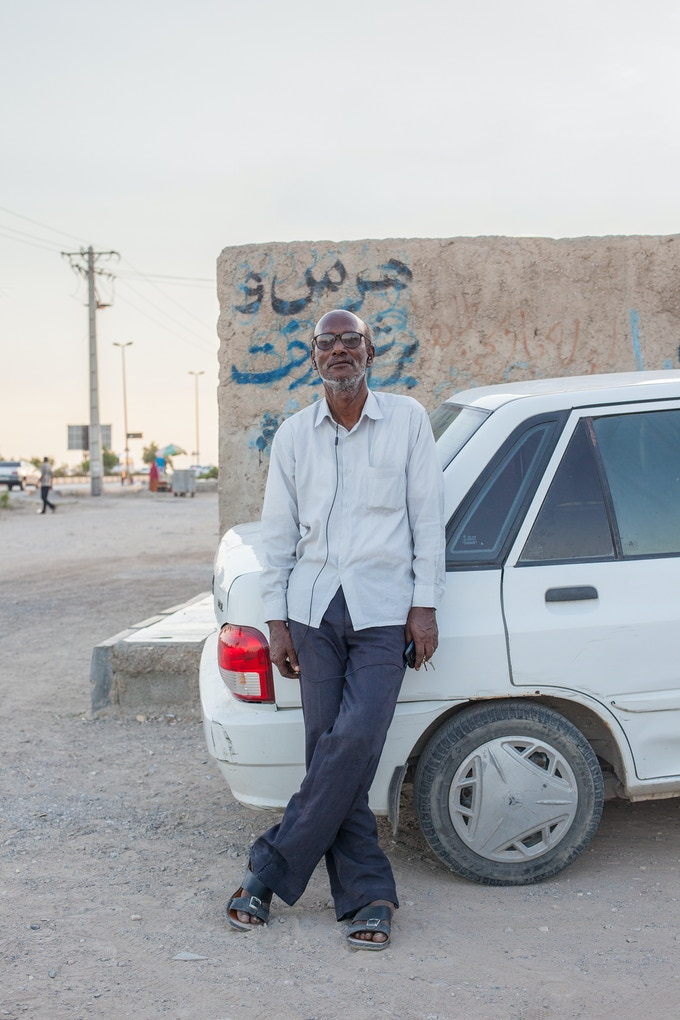 A man leaning against one of the most sold cars in Iran, a Kia Pride. The nearly extinct cult car is the Peykan.