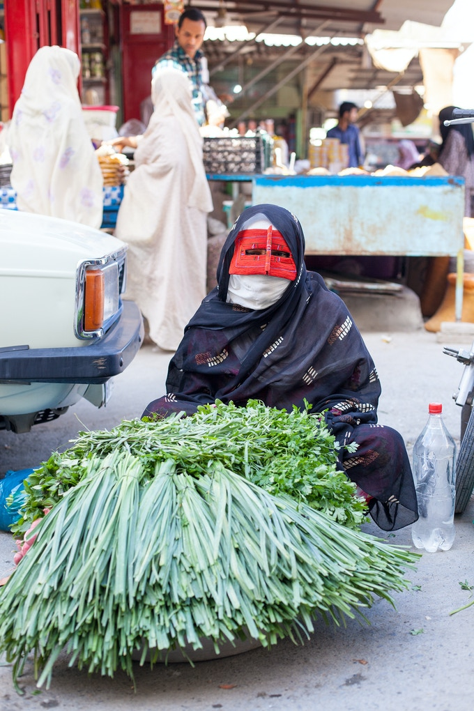 A woman wearing a traditional mask named Borkeh selling vegetables at the Thursday's Bazar Market in Minab, one of the cities near Bandar Abbas (Capital of Hormozgan).
