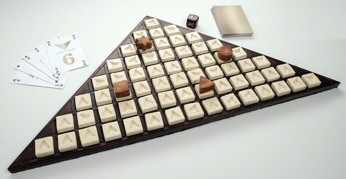 Photograph of the prototype, the board and the hand-made wooden die, ceramic game stones, pawns made of modelling clay and the cards made of cardboard.