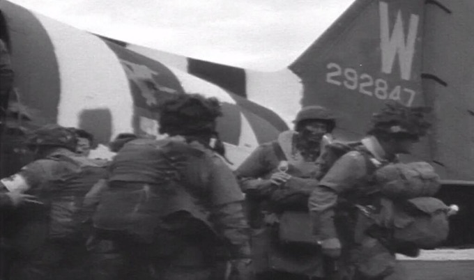 The faces of the paratroopers were camouflaged chocolate brown. Also, note the black & white stripes on the aircraft tail, applied hurriedly as a special provision for the invasion.
