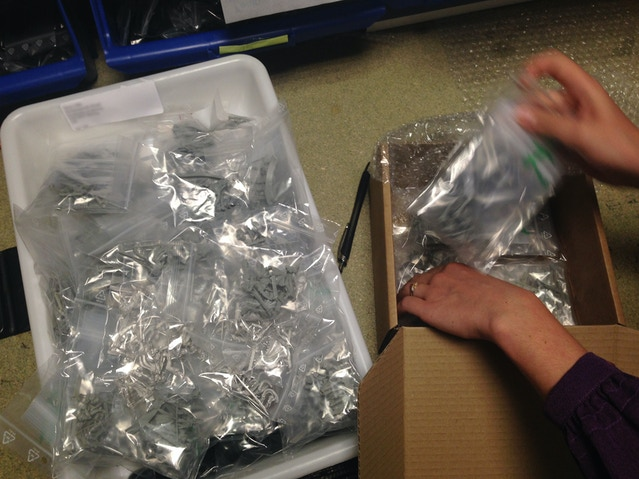 Here, we carefully layer the minis in a shipping box.