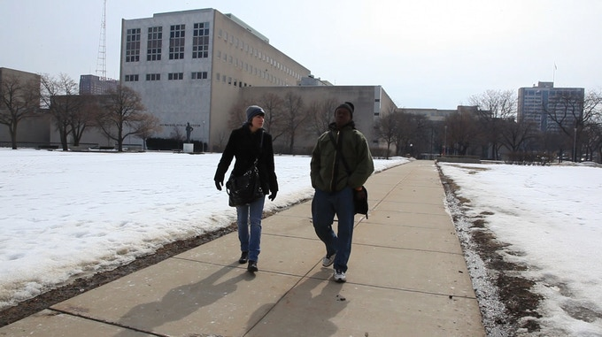 "Faith Kohler and Harold Sloan walking ""the trail"" downtown Milwaukee. The homeless community in Milwaukee call this ""the trail"" because it is their daily pathway between shelters, meal sites, and various social service providers."