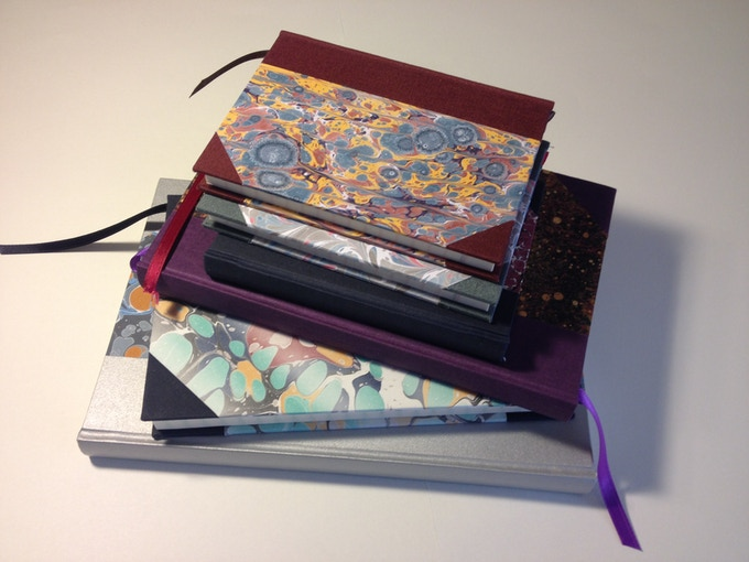 An assortment of hand-bound journals with marbled Paper