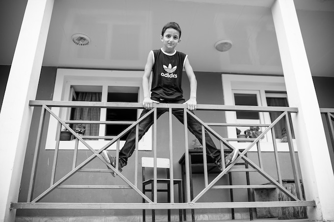 Brave Georgian youth climbing the rails in front of a Children's House