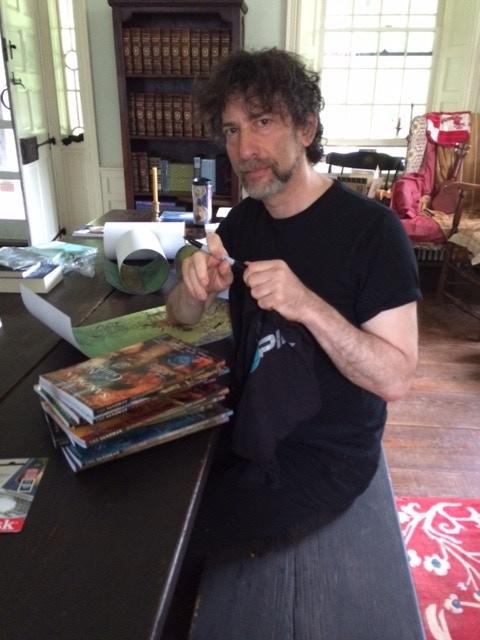 "Neil Gaiman signing the complete ""Sandman"" series, a MYOPIA T-shirt and ""Desert Wind"" prints"