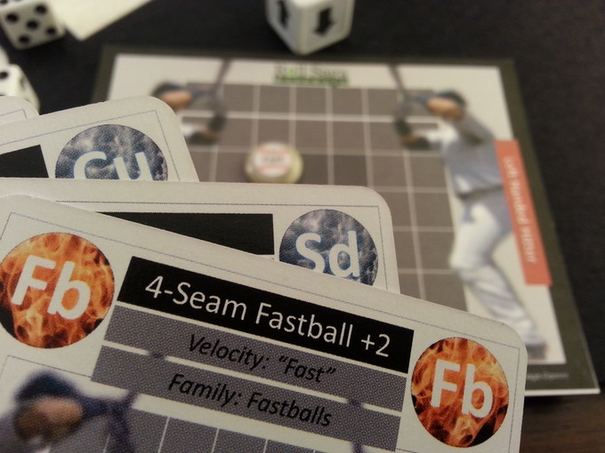 Close up of pitch cards held in hand (showing the 4 Seam Fastball +2) with the pitch pad in the background