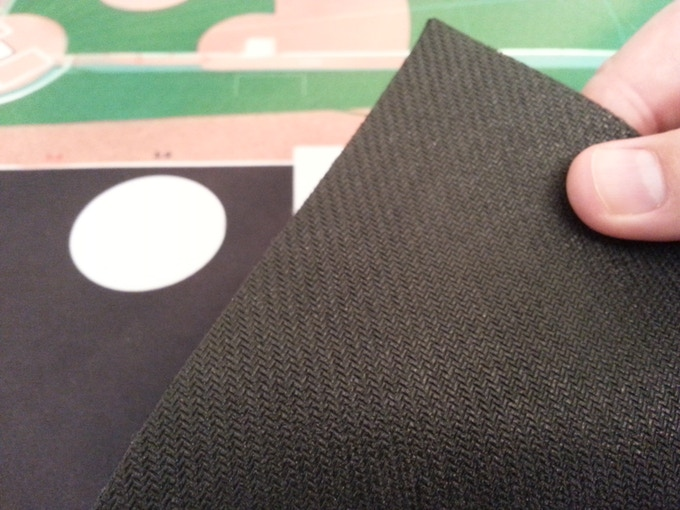 The rubber backing of the game mat prevents sliding and cushions the playing and rolling area for soft dice rolls.