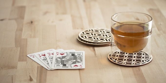 A set of 4 unique birch ply coasters with intricate geometric patterns from Indian screens (jali) - Each coaster is made in Toronto by Hot Pop Factory and is flippable (with a natural finish and dark finish), so your coasters can look good on every table.