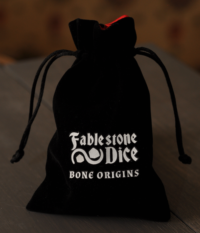 The Bone Origins velvet dice bag features the Fablestone Dice logo and has a red satin lining to protect your dice.