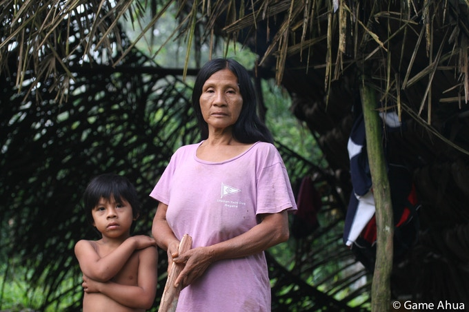 Yedo Ciaga and her grandson Memo stand in front of a traditional Waorani house that her son Nonge Ahua made from natural resources in the jungle around their community of Ganketapare in Yasuní Biosphere Reserve.