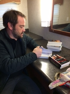 """Ruth Connell taking a picture of Mark Sheppard signing """"Supernatural"""" novels for the MYOPIA Kickstarter"""