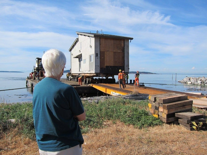 A house recycled by OPAL is transferred off the barge onto the island.