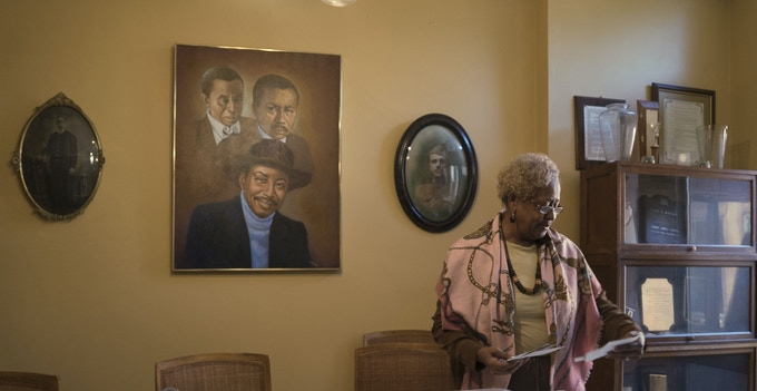 Charmaine McKissick-Melton, current Soul City resident and daughter of Soul City founder Floyd B. McKissick, digs through photos at the family home.