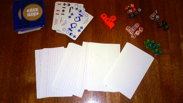 Six sided dice of a few different colors, the Deck of Fate (or Fate Dice), and notecards are needed to play.