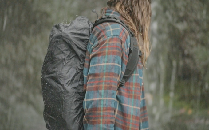 The rainfly is fitted to the pack, but leaves enough room for the accessories you have strapped to the outside of bag to fit under there as well.